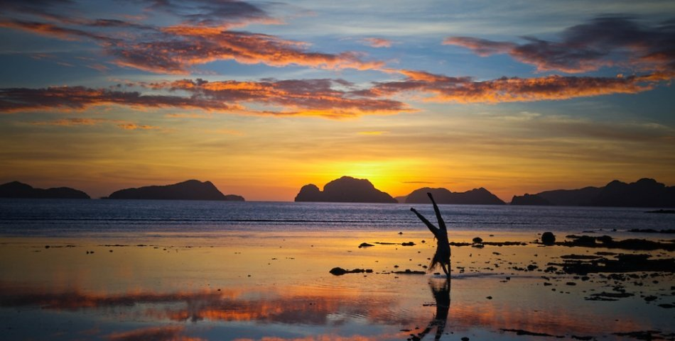 At Las Cabanas Beach near El Nido on the island of Palawan in the Philippines, a girl does a cartwheel over the shallow water causing a reflection during the best sunset this photographer has ever seen.